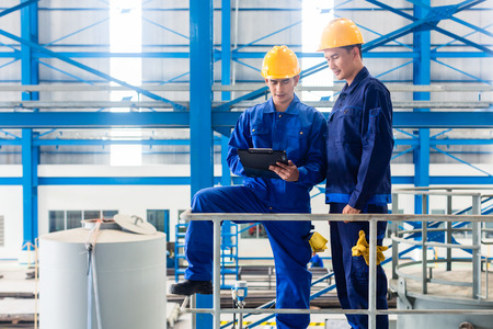 engineering clipboard: Two workers in large metal workshop or factory checking work standing on large machine