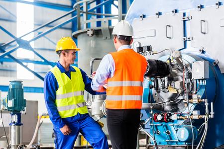 supervisores: Trabajador y gestor en fábrica industrial discutir la aceptación de la máquina