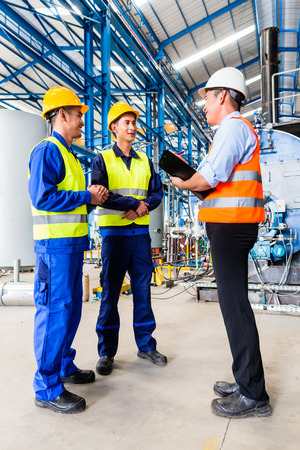 or instruction: Asian factory worker and engineer as team inspecting a machine delivery Stock Photo