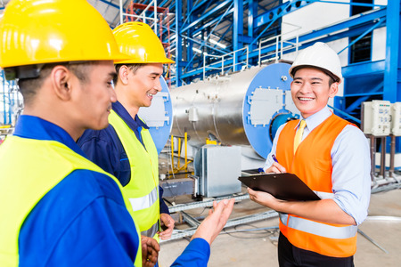 Asian factory worker and engineer as team inspecting a machine delivery Stock Photo