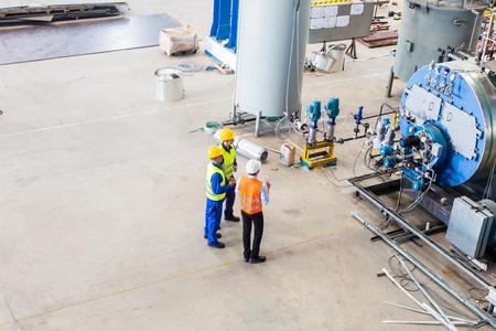 Industriële team van Worker en ingenieur bespreken aan de machine in de fabriek