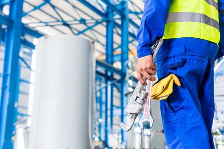 Industriële arbeider in de fabriek met gereedschappen gaat machineonderhoud