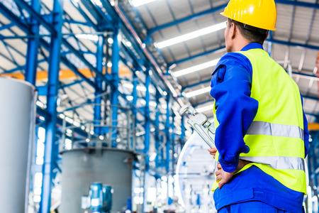 Fabrieksarbeider in Aziatische fabriek met gereedschappen gaan machineonderhoud