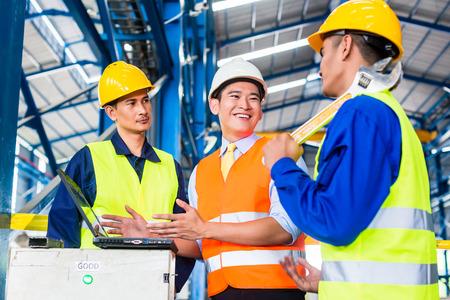 労働者とノート パソコン生産の訓練で工場のエンジニアのチーム 写真素材