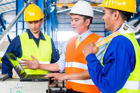 supervisi�n: Personas de los trabajadores y el ingeniero en la f�brica en el entrenamiento de producci�n con el ordenador port�til
