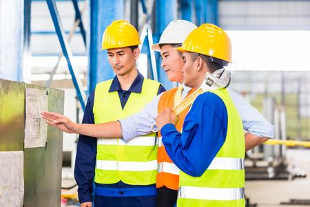 empleados trabajando: Personas de los trabajadores y el ingeniero en la f�brica en el entrenamiento de producci�n con el ordenador port�til