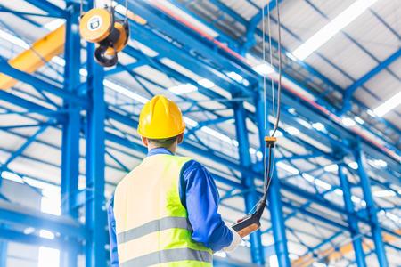 Arbeider in de fabriek het beheersen kraan met afstandsbediening Stockfoto