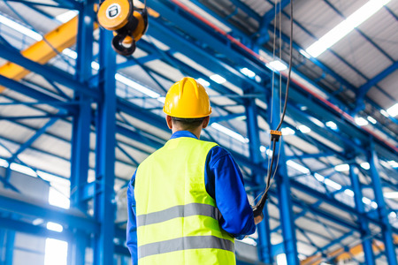steel factory: Worker in factory controlling crane with remote