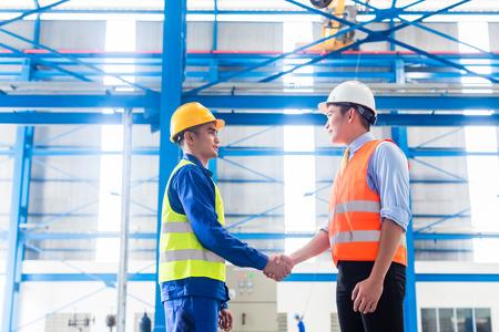ワーカーと握手の工場で契約を有する顧客