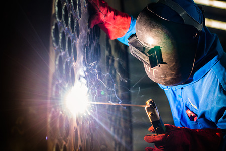 Welder working in an industrial setting manufacturing steel equipment photo