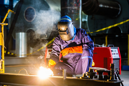 Welder working in an industrial setting manufacturing steel equipment