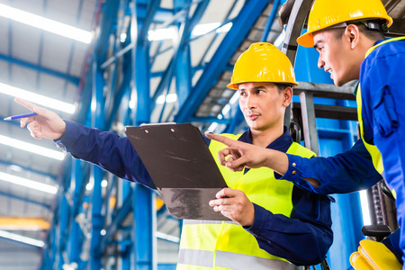 industries: Worker and forklift driver in industrial factory looking at camera