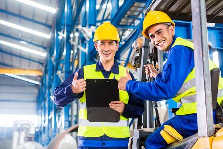 Werker en heftruckchauffeur in industriële fabriek kijken naar de camera