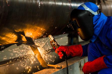 metal pipes: Welder in factory welding metal pipes Stock Photo