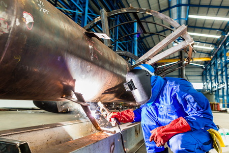 welding metal: Welder in factory welding metal pipes Stock Photo