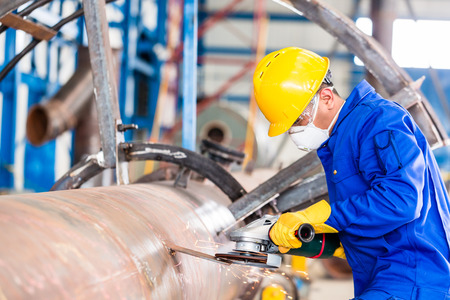Industrial worker in manufacturing plant grinding to finish a pipeline photo