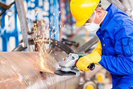 industries: Industrial worker in manufacturing plant grinding to finish a pipeline