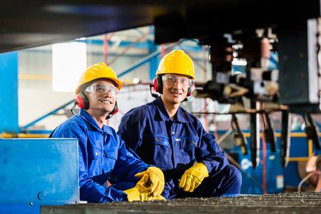 Werknemer in Aziatische fabriek op industriële metalen snijbrander machine