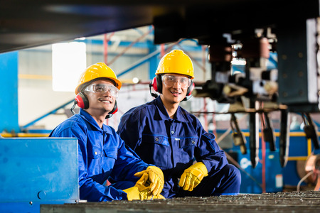 Worker in Asian factory at industrial metal cutting torch machine photo