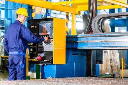 tablero de control: Trabajador en la planta de fabricación en el panel de control de la máquina CNC