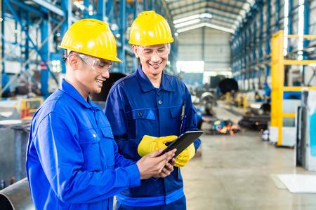supervisores: Dos trabajadores de la planta de producción como equipo en discusiones, escena industrial en el fondo Foto de archivo