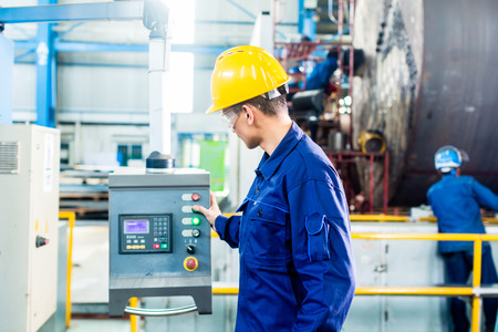 Worker in factory at CNC machine control panel