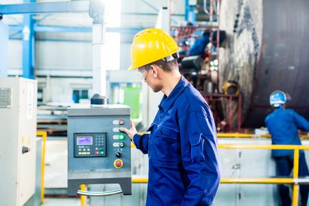 tablero de control: Trabajador en la fábrica en el panel de control de la máquina CNC