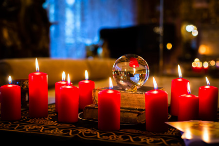 Crystal ball to prophesy or esoteric clairvoyance during a Seance in the candle light Foto de archivo