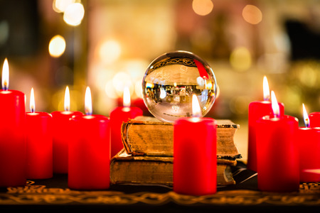 clairvoyance: Crystal ball to prophesy or esoteric clairvoyance during a Seance in the candle light Stock Photo
