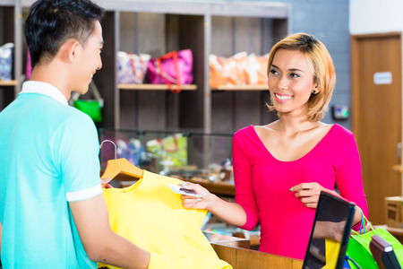 Asian woman paying purchase in fashion store with credit card Stock Photo