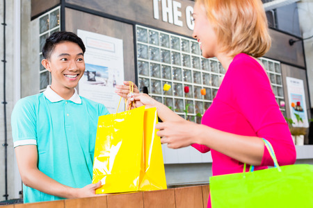 customer assistant: Shop assistant handing purchase in shopping bags to Asian woman