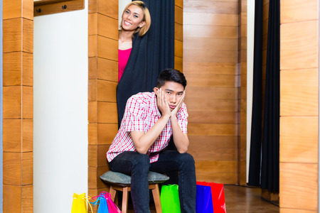 Asian Man waiting for woman in front of dressing room, he is bored photo