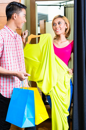 Asian couple in fashion store at dressing room, she is handing him dresses photo