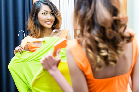 Asian woman choosing dress in store fitting room, looking at herself in the mirror