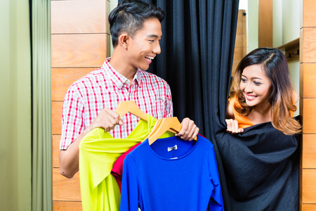 Asian couple shopping fashion in clothes store, she is in the dressing room photo