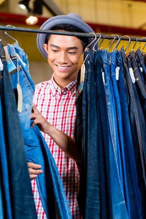 男性ファッションの店で服のラックに掛かっているジーンズを参照