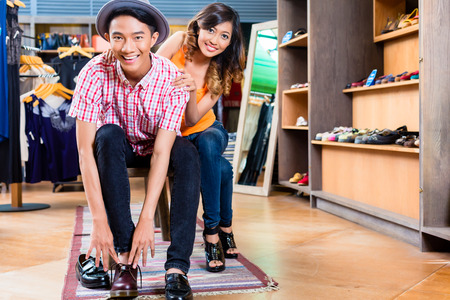 trying on: Asian couple buying shoes in store or shop Stock Photo