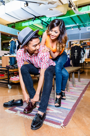 buying: Asian couple buying shoes in store or shop Stock Photo