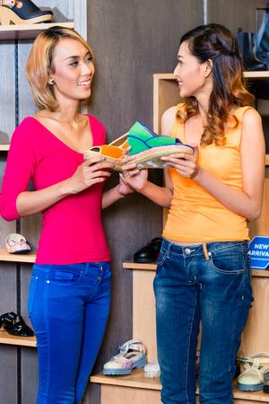 comprando zapatos: Compras asiáticas amigas de zapatos en la tienda
