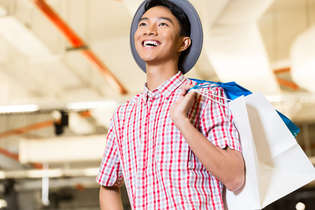 adult indonesia: Asian young man shopping fashion in store being visibly happy