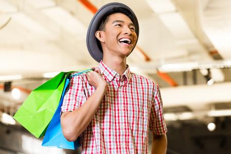Aziatische jongeman winkelen mode in de winkel zijn zichtbaar blij Stockfoto