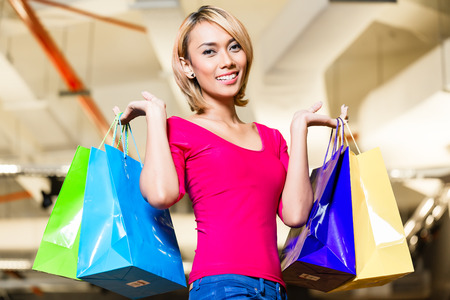Asian young woman shopping fashion in store with lots of bags over her shoulders photo