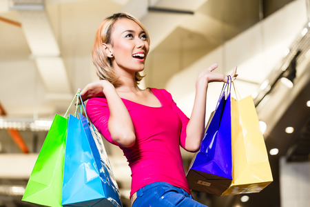 asian girl shopping: Asian young woman shopping fashion in store with lots of bags over her shoulders