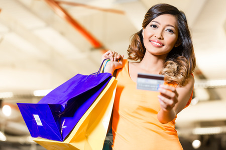 adult indonesia: Asian young woman in fashion store or shop paying with credit card Stock Photo