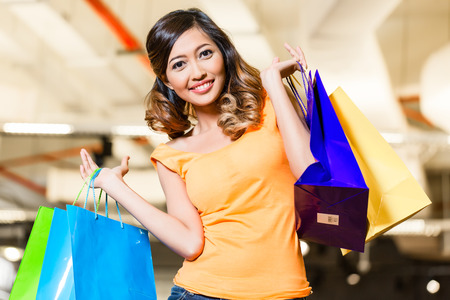 adult indonesia: Asian young woman shopping fashion in store with lots of bags over her shoulders