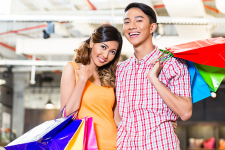 Asian couple shopping in fashion store or shop with lots of bags Stock Photo