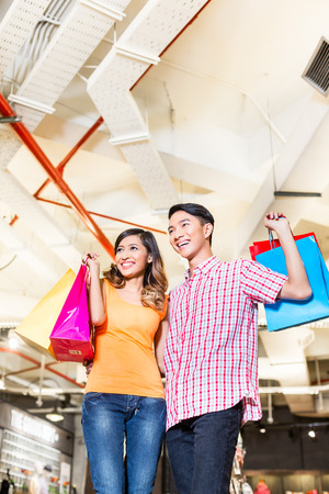 adult indonesia: Asian couple shopping in fashion store or shop with lots of bags Stock Photo