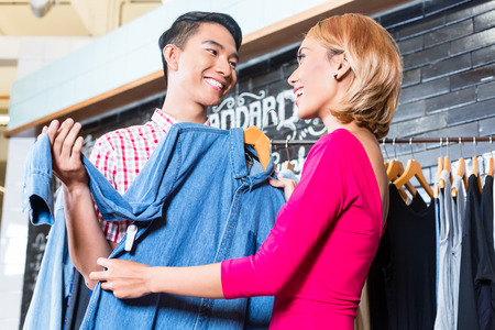 Asian couple, man and woman, shopping in fashion store or shop photo