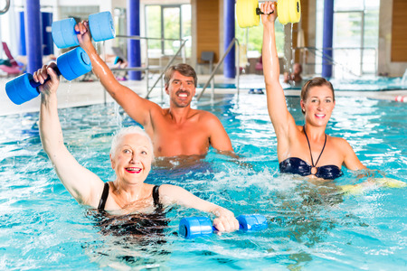 hydrotherapy: Group of people, mature man, young and senior women, at water gymnastics or aquarobics Stock Photo
