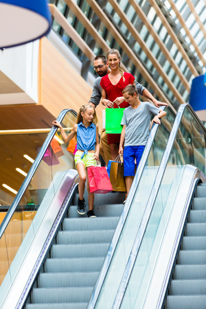 Family in shopping mall on escalators with bags photo